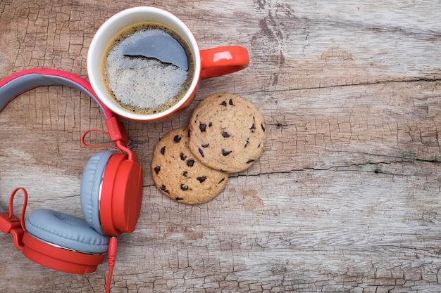 Tasse à café rouge, écouteurs rouges et biscuits au chocolat sur la table en bois. vue de dessus. café avec concept chirstmas. Photo gratuit