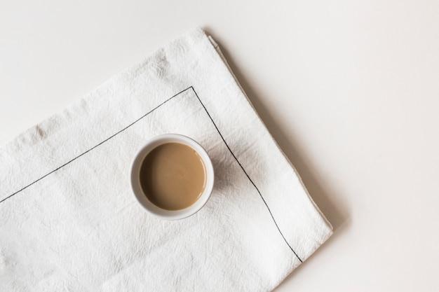 Tasse de café sur serviette sur fond coloré Photo gratuit