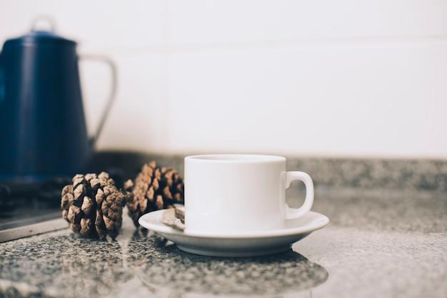 Tasse de café sur la soucoupe et pomme de pin sur le comptoir de la cuisine sur fond blanc Photo gratuit