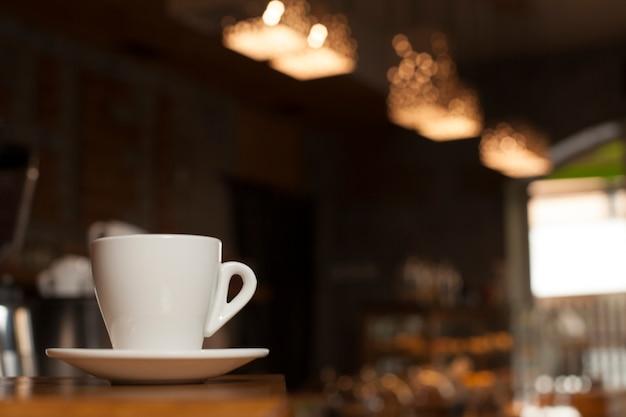 Tasse de café avec soucoupe sur table avec fond de café de flou Photo gratuit