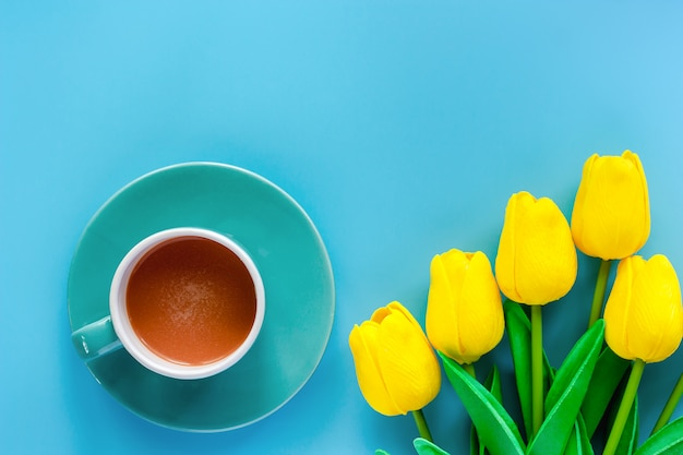 Tasse De Café Avec Soucoupe Et Tulipes Jaunes Artificielles Sur Fond Bleu Photo Premium