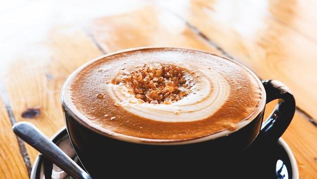 Tasse à café sur la table / tasse à cappuccino avec art au latte et sucre sur le dessus Photo Premium