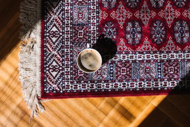 Tasse de café sur le tapis Photo gratuit