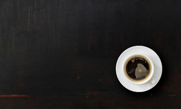 Tasse de café sur la texture du bois peint noir Photo Premium