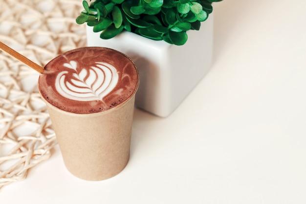 Tasse, de, cappuccino, dans, une, tasse papier, à, a, modèle, sur, a, table, dans, a, café, copie espace Photo Premium