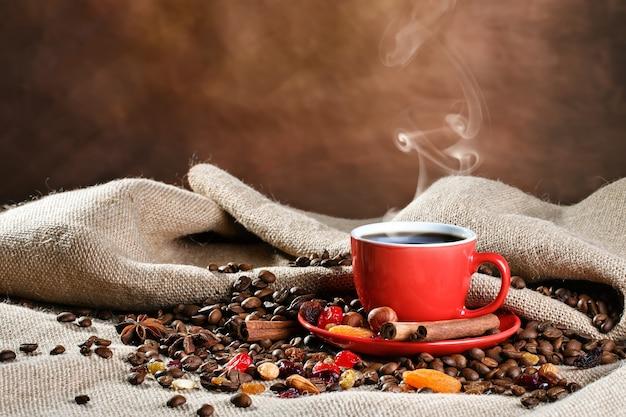 Tasse en céramique rouge avec café chaud sur des planches en bois. Photo Premium