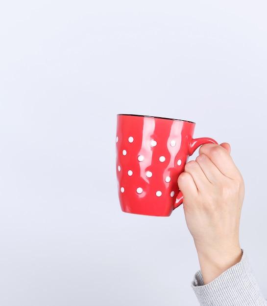 Tasse en céramique rouge dans une main féminine sur une surface blanche Photo Premium