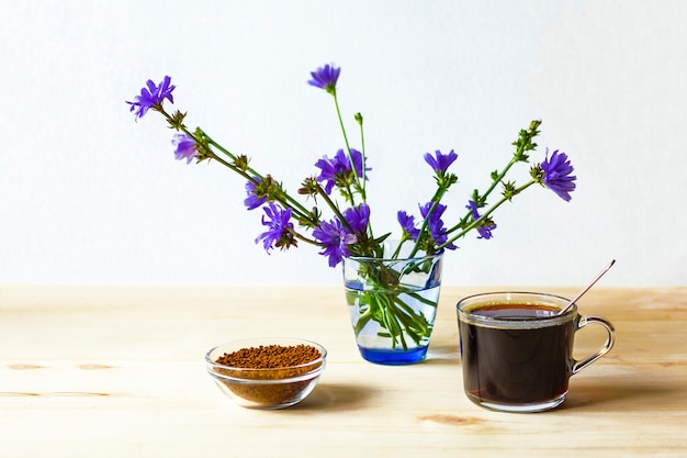 Une Tasse De Chicorée, Des Granulés De Chicorée Instantanée Lyophilisée Et Des Fleurs Bleues Photo Premium