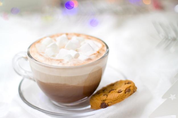 Tasse de chocolat chaud au cacao avec des biscuits à la guimauve et au pain d'épice lumières brouillées Photo Premium