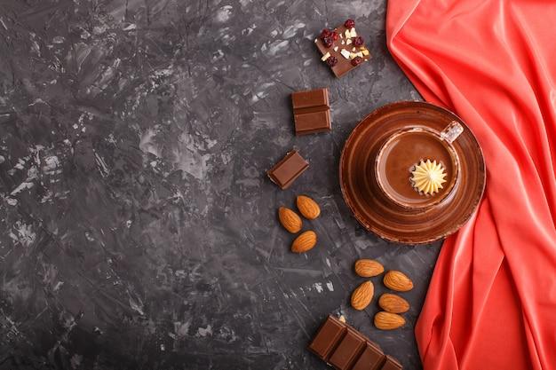 Tasse de chocolat chaud et des morceaux de chocolat au lait avec des amandes sur un fond de béton noir avec textile rouge. Photo Premium