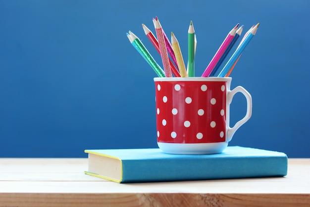 Tasse avec des crayons de couleur et livre sur une table en bois sur un fond bleu. Photo Premium