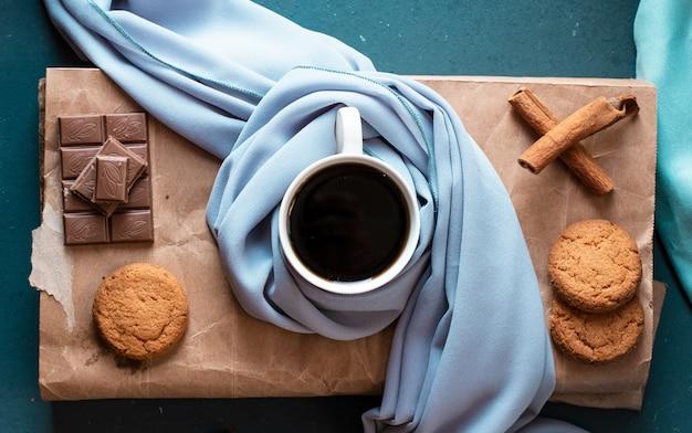 Une tasse d'espresso noir à la cannelle, des biscuits et une barre de chocolat. vue de dessus. Photo gratuit