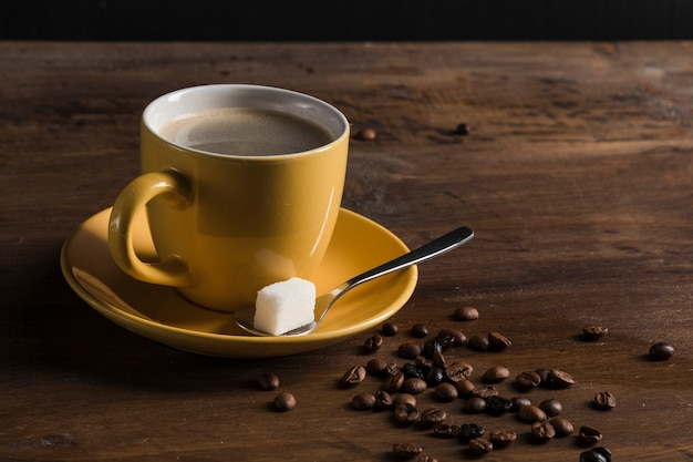 Tasse jaune de café et assiette avec un cube de sucre Photo gratuit