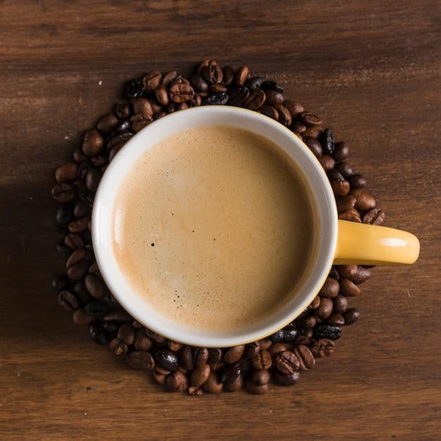 Tasse jaune avec grains de café autour Photo gratuit