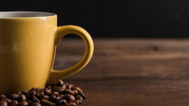 Tasse jaune avec grains de café Photo gratuit