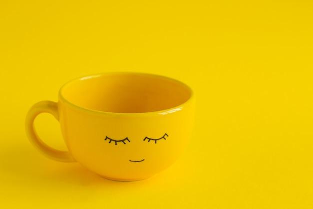 Tasse jaune avec joli visage souriant sur jaune Photo Premium