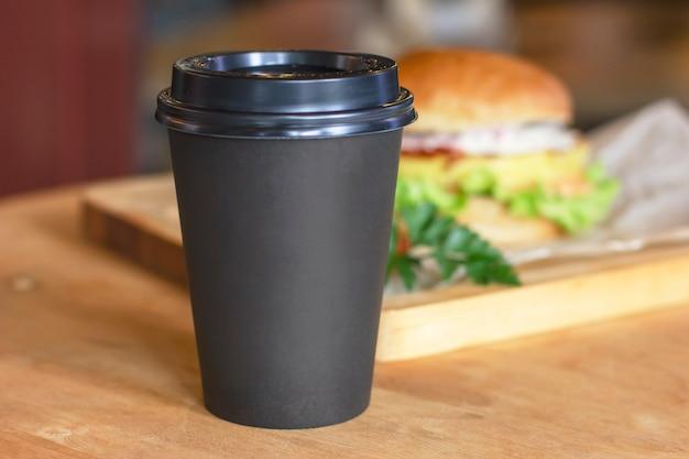 Tasse noire avec café pour aller sur fond avec hamburger, maquette Photo Premium