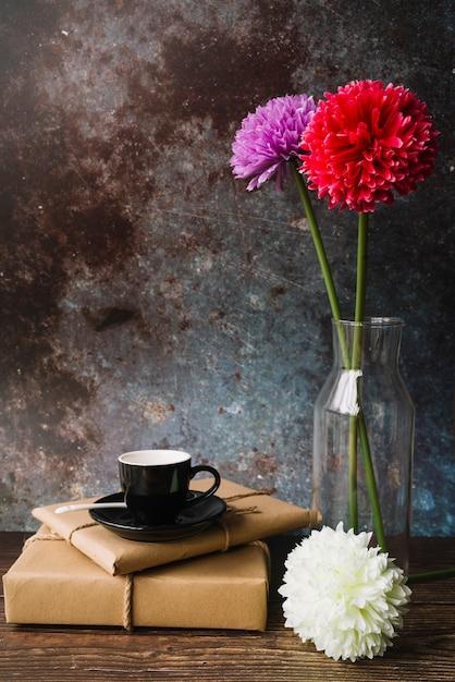 Tasse noire et soucoupe sur des boîtes de cadeau en papier brun emballé avec de belles fleurs Photo gratuit