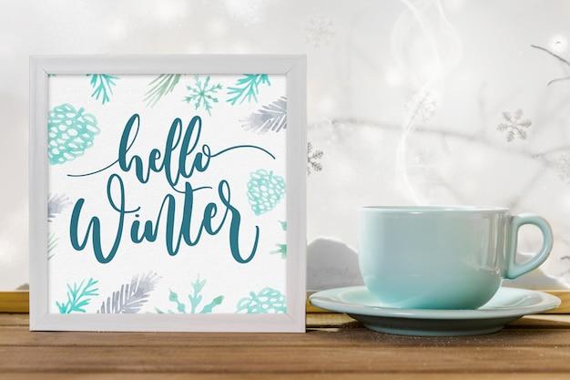 Tasse près du cadre avec titre d'hiver sur la table en bois près de la berge de la neige Photo gratuit