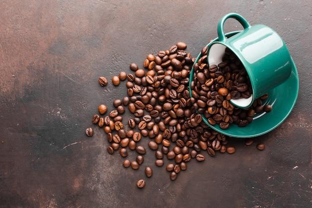 Tasse renversée avec grains de café Photo gratuit