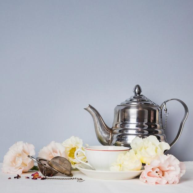 Tasse à thé avec arrangement de fleurs Photo gratuit