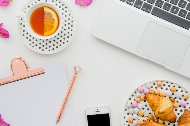 Tasse de thé au citron; portable; croissant; des sucreries; téléphone portable; stylo et presse-papiers sur fond blanc Photo gratuit