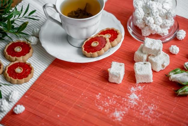 Tasse de thé aux fruits chaud et pain d'épices de noël sur plateau avec anis et noisettes. Photo Premium