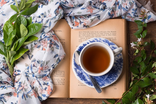 Tasse à thé aux herbes et soucoupe sur un livre ouvert avec feuilles et écharpe sur la table Photo gratuit