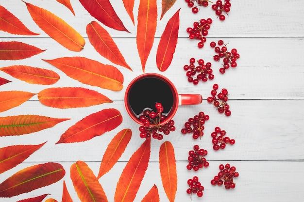 Tasse De Thé Avec Des Baies De Viorne Et Des Feuilles D'automne Rouges Sur Une Planche De Bois. Photo Premium
