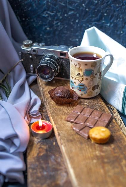 Une tasse de thé avec une barre de chocolat et des muffins sur un morceau de bois. Photo gratuit