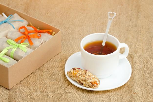 Tasse de thé, une barre de muesli et des boîtes de barres. toile à sac Photo Premium