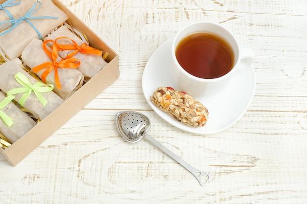 Tasse de thé, barres de muesli et passoire à thé. boîte à barres. fond en bois blanc Photo Premium