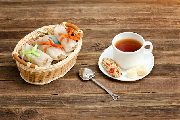 Tasse de thé, barres de muesli et passoire à thé. panier en osier avec des barres. fond en bois marron Photo Premium