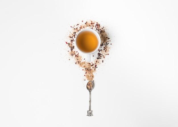 Tasse à thé à base de plantes entourée d'herbes de thé séchées et cuillère sur fond blanc Photo gratuit