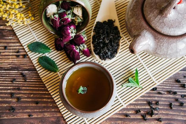 Tasse à Thé à Base De Plantes Avec Fleur De Rose Séchée Et Feuilles Sèches Sur Napperon Photo gratuit