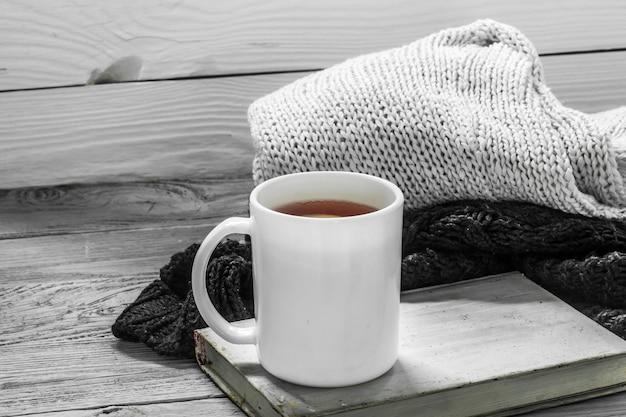 La Tasse De Thé Sur Un Beau Fond En Bois Avec Pull D'hiver, Vieux Livre, Hiver, Automne, Gros Plan Photo gratuit