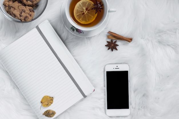 Tasse à thé avec des biscuits près du bloc-notes et smartphone Photo gratuit
