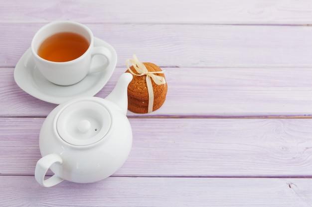 Tasse de thé avec des biscuits sur une surface en bois lilas Photo Premium