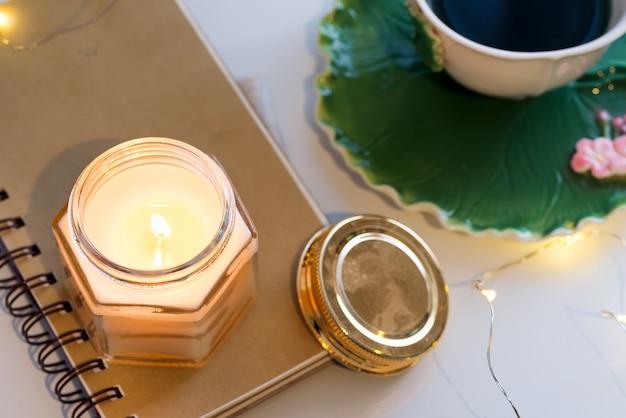 Tasse De Thé Et Bougies Aromatiques Sur Un Ordinateur Portable Sur Un Tableau Blanc Photo Premium