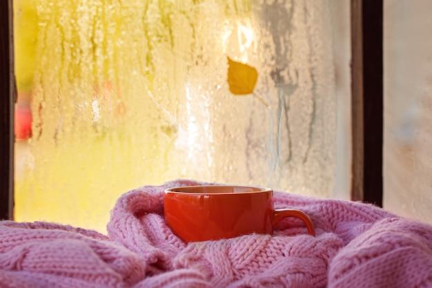 Tasse de thé ou de café en automne et feuilles jaunes sur la fenêtre des pluies Photo Premium