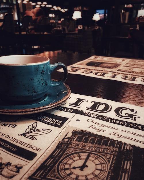 Une tasse de thé ou de café, un bar, un restaurant, un journal. Photo Premium