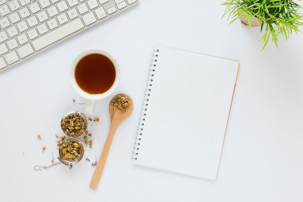 Tasse de thé avec cahier sur table blanche Photo gratuit