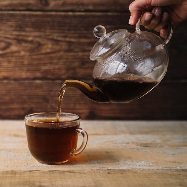Tasse de thé chaud étant rempli d'une théière Photo gratuit