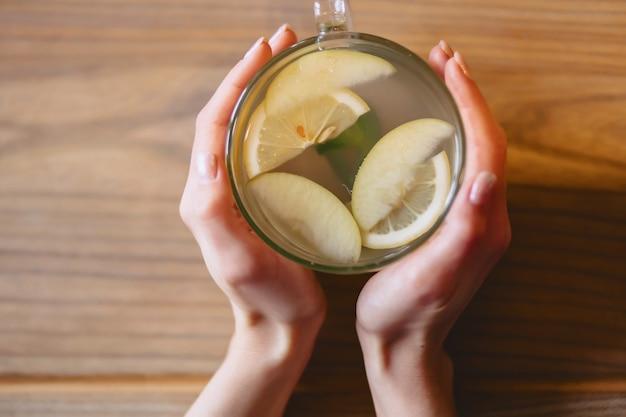 Une tasse de thé chaud à la menthe et citron dans les mains des femmes Photo Premium