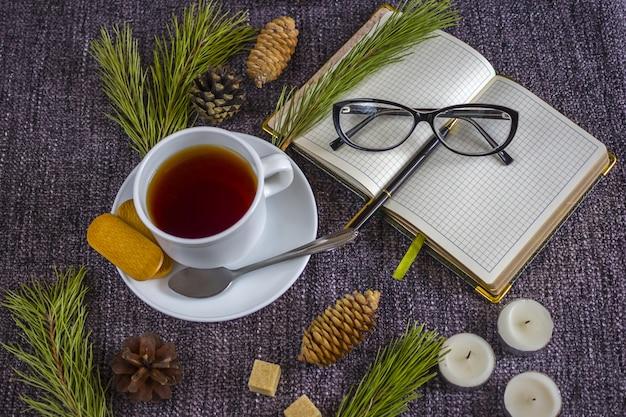 Tasse de thé chaud parfumé parmi les branches d'arbre de noël et les pommes de pin sur un plaid. Photo Premium