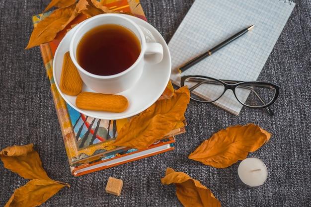 Tasse de thé chaud parfumé parmi les feuilles jaunes sur un plaid. Photo Premium
