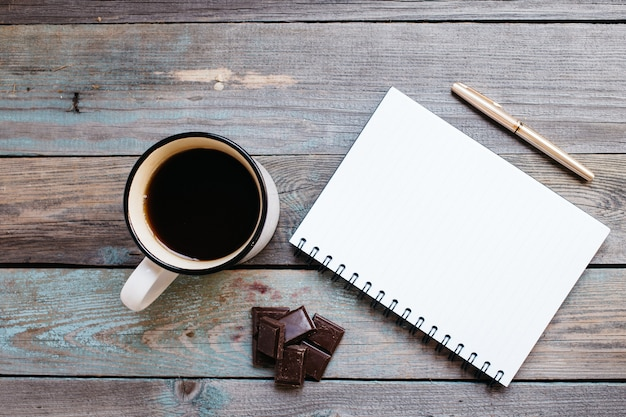 Tasse de thé, chocolat et stylo, cahier sur une table en bois, flatlay Photo Premium