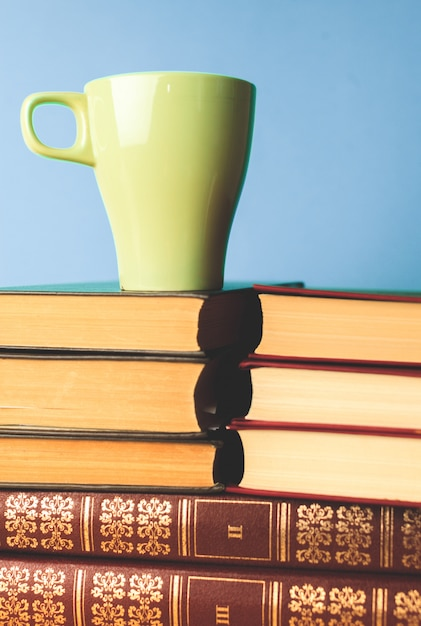 Tasse de thé de couleur avec des livres sur la table Photo Premium