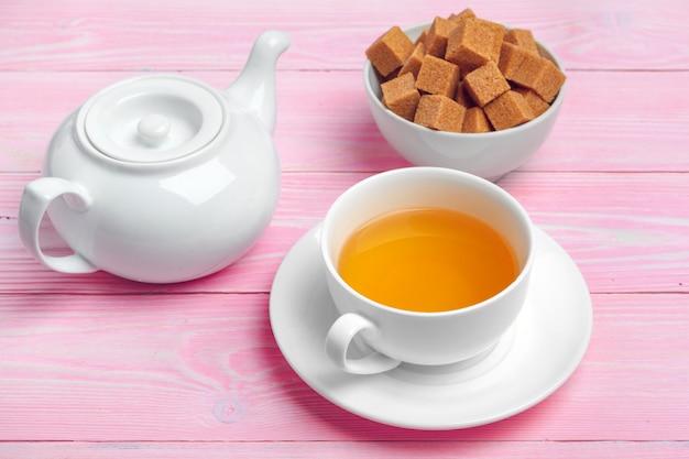 Tasse de thé avec des cubes de sucre et des branches de fleurs sur une table en bois se bouchent Photo Premium