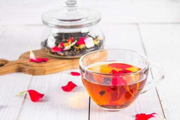 Une tasse de thé, dans le fond d'une banque avec un thé floral noir sur une table en bois blanche. Photo Premium